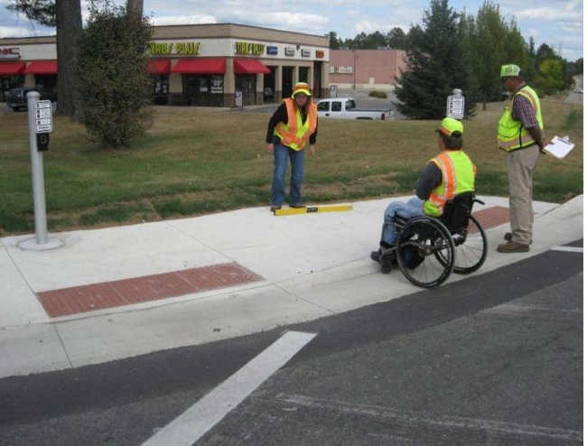 Three people inspecting a curb ramp at a street intersection